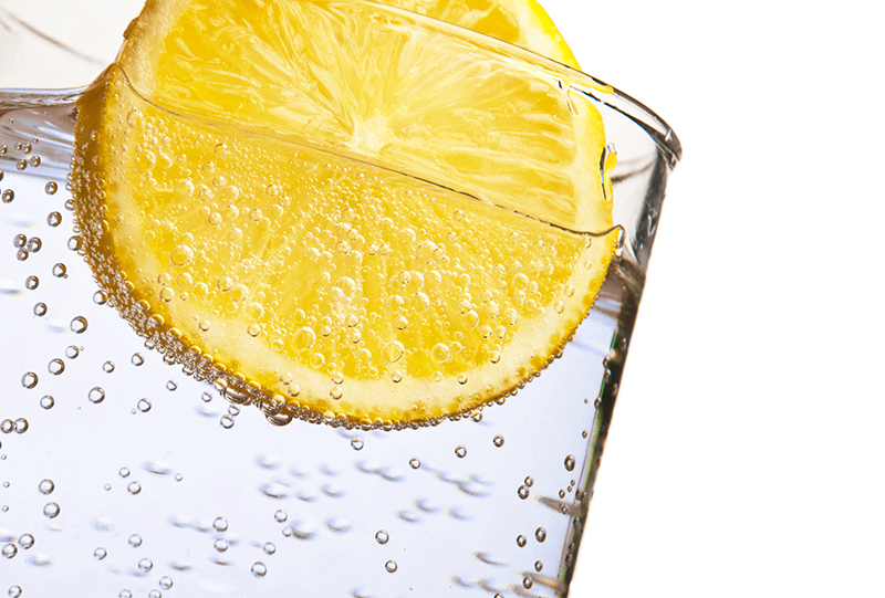 Soda water with lemon isolated on white